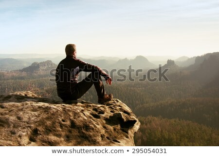 молодым человеком сидят край утес глядя реке Сток-фото © photobac
