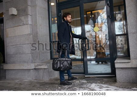 Businessman standing office building holding jacket Stock photo © HASLOO