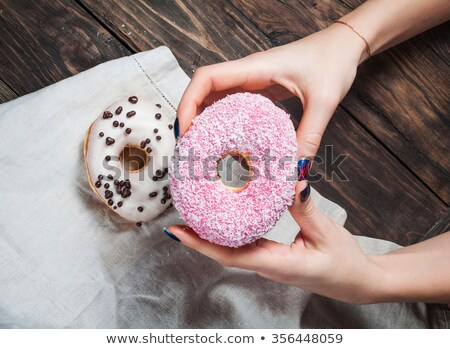 Hand reaches for sweet sugary donut on rustic table Stock photo © stevanovicigor