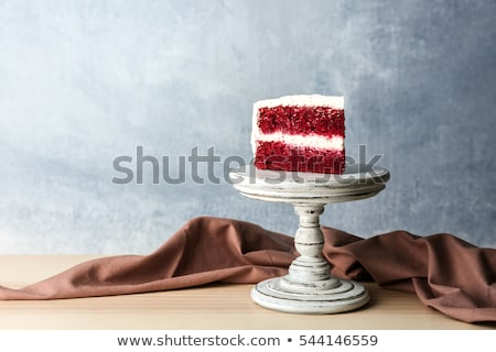 fresh tasty sweet piece of red velvet cake on a white napkin and a dessert fork on a wooden backgr stock photo © mcherevan