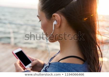 Beautiful adult caucasian woman using mobile phone on seaside va Stock photo © stevanovicigor