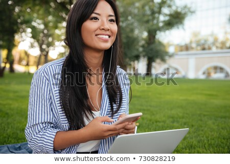 smiling young asian girl outdoors in park looking aside chatting by phone stock photo © deandrobot