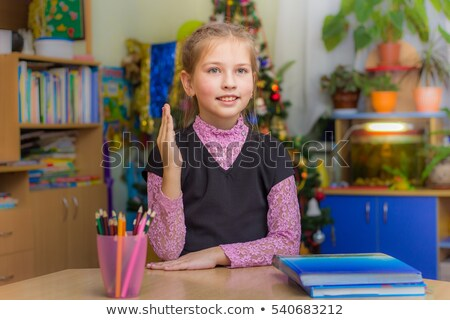 Rear view of schoolkids raising hands and sitting at desk in classroom of elementary school Stock photo © wavebreak_media