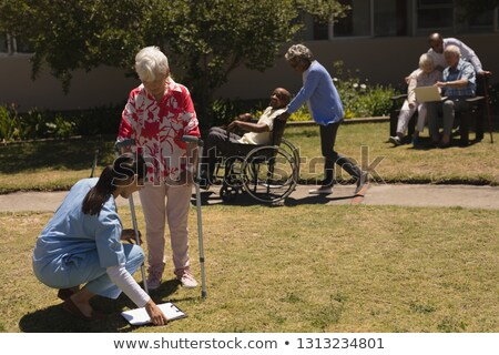 Stock photo: Front view of young female doctor kneeling and examining in front of disabled senior woman in garden