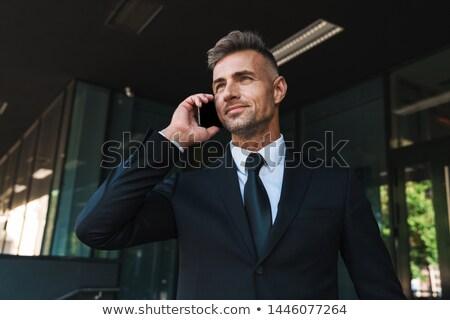 Fotografia przystojny dojrzały mężczyzna uśmiechnięty mówić Zdjęcia stock © deandrobot