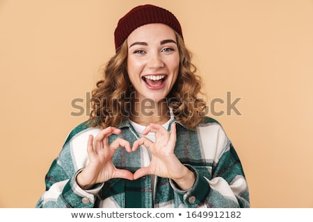 Photo of nice funny woman in knit hat smiling and gesturing heart sign Stock photo © deandrobot