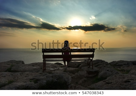 silhouette of a sad lone woman on cliff edge stock photo © morrbyte