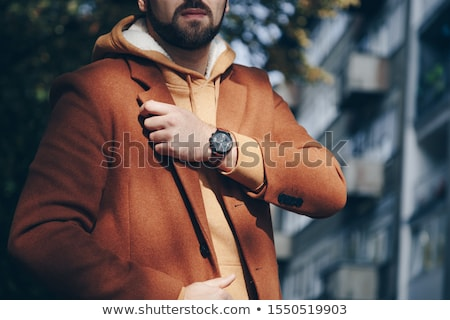 casual young man checking his wrist watch stock photo © photography33