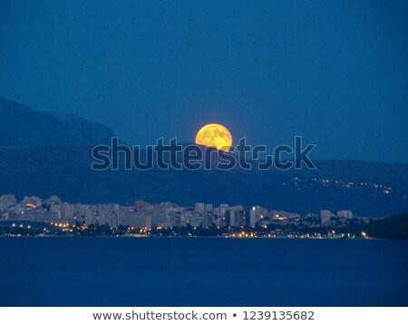 Maan achter bergen volle maan zee nacht Stockfoto © Onyshchenko