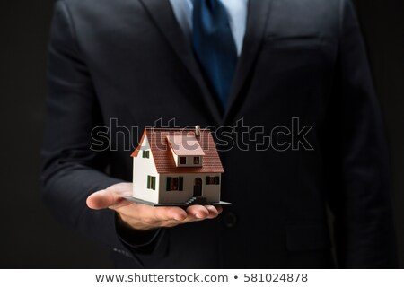 Businessman Holding Model House In Palm Of Hand Stock photo © HighwayStarz