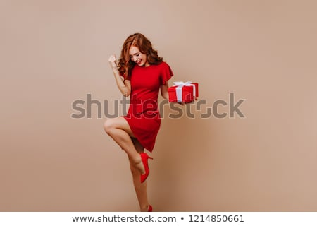 Attactive smiling young woman in red shoes with high heels  Stock photo © deandrobot