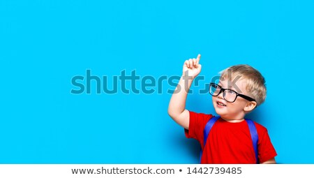 student child with a book and glasses over his head isolated ove stock photo © zurijeta