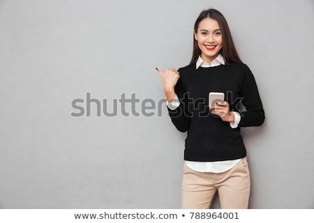 Mosolyog barna hajú nő tart okostelefon másfelé néz Stock fotó © deandrobot