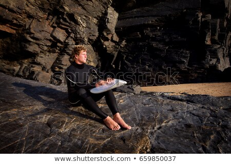 Man sitting on large rock in wetsuit Stock photo © IS2