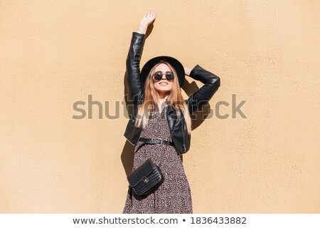 Girl in sunglasses and a hat stands near the wall Stock photo © Alones