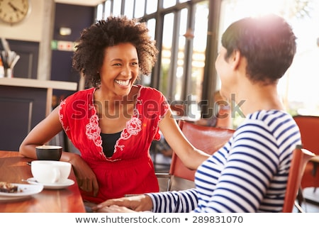 happy young friends talking with each other drinking coffee outdoors winter concept stock photo © deandrobot
