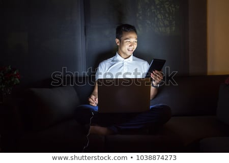 tired businessman with laptop at night office stock photo © dolgachov