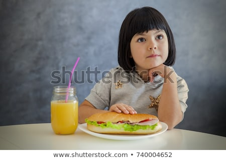 Cute black hair little girl having breakfast and drinking orange Stock photo © boggy