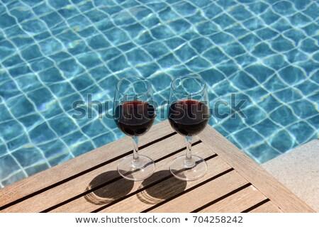 Glass of red wine in poolside Stock photo © brebca