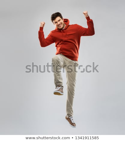 smiling young man in red hoodie over grey Stock photo © dolgachov