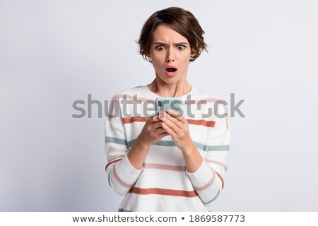 Photo of confused beautiful woman holding sweater and looking at camera Stock photo © deandrobot