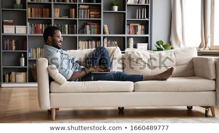 Young man lying on couch with computer Stock photo © photography33