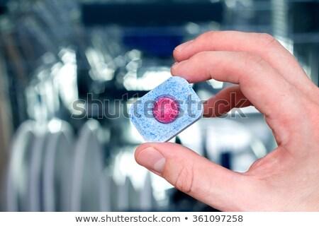 Hand holding dishwashing tablet. Dishwasher in background Stock photo © simpson33