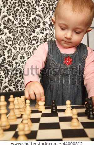 Portrait of little girl in denim dress playing chess. Vertical format. Indoor. Stock photo © Paha_L
