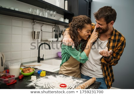 Happy couple kneading dough and baking together on kitchen Stock photo © deandrobot
