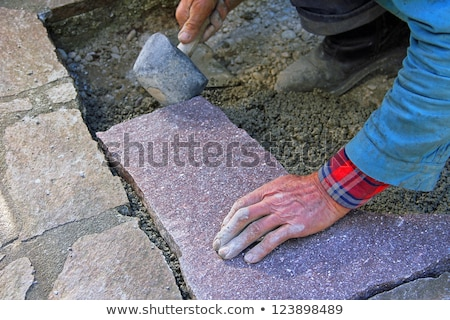 Worker hand on flagstone Stock photo © simply