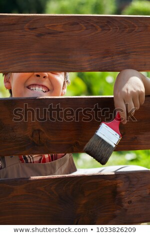 Boy having fun grimacing through a fence - while painting it Stock photo © ilona75
