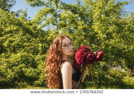 Young girl with ginger hair hold beautiful bunch with fresh natural flowers and leaves on a light ba Stock photo © artjazz