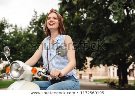 Picture of Smiling hipster woman sitting on scooter and looking Stock photo © deandrobot