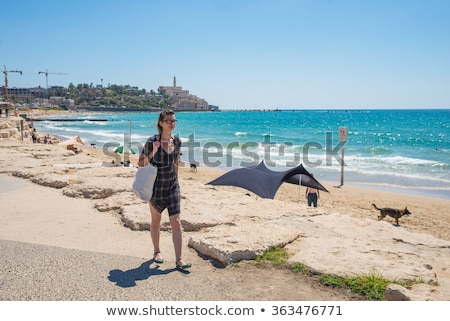 Girl walking along the seafront in dress in hot summer day Stock photo © ElenaBatkova