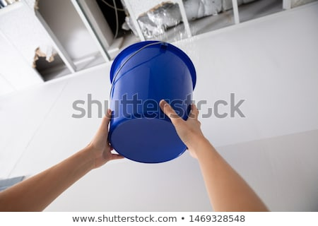 Woman Holding A Blue Bucket Under The Leak Ceiling Stock photo © AndreyPopov