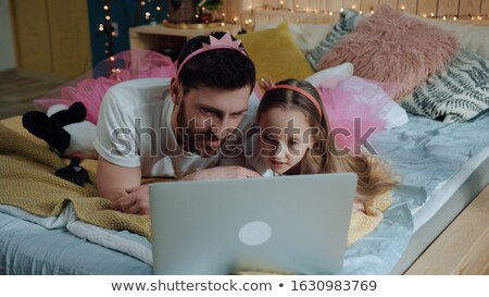Happy young father and his daughter watching funny video in smartphone Stock photo © pressmaster