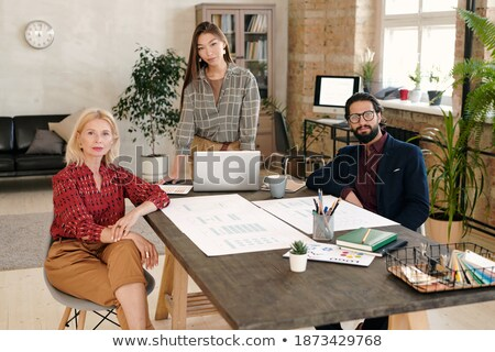 two young businessmen sitting by wooden table while discussing documents stock photo © pressmaster