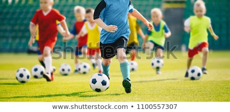 Running soccer players in duel. Youth athletes kicking ball Stock photo © matimix