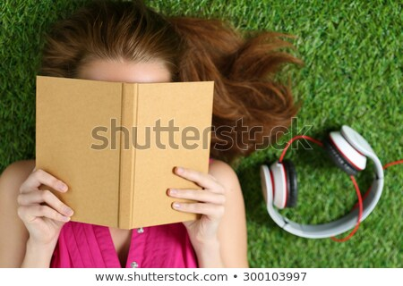 Stock photo: Teen Girl Reads Book Laying On Grass