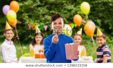 smiling boy eating popcorn at birthday party Stock photo © dolgachov