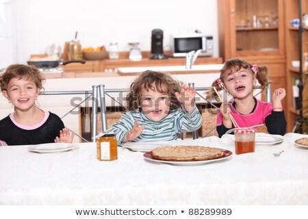 Three children gathered around breakfast table Stock photo © photography33