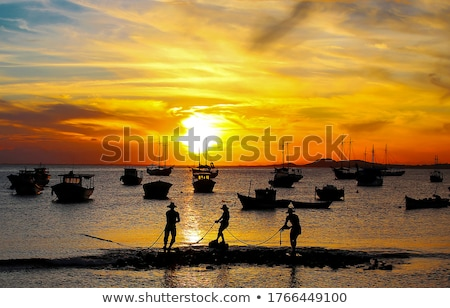 Silueta pescador pesca puesta de sol océano paisaje Foto stock © dinozzaver