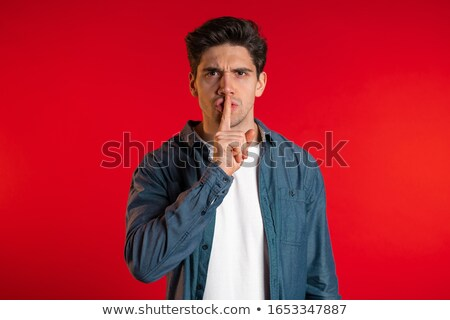 Young male holds finger on his lips Stock photo © stockyimages