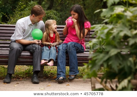 Parents together with daughter on bench in park in afternoon. Parents inflate multi-coloured balloon Stock photo © Paha_L