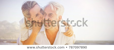 romantic married couple kissing and hugging on the beach stock photo © deandrobot