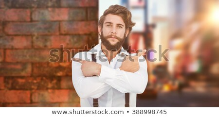 Hipster pointing sideways with arms crossed Stock photo © wavebreak_media