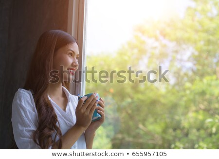 Woman standing by a window stretching Stock photo © IS2