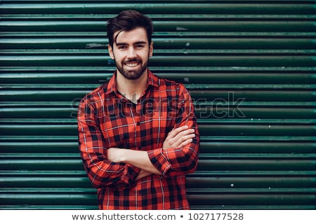 portrait of a cheerful young man in plaid shirt stock photo © deandrobot