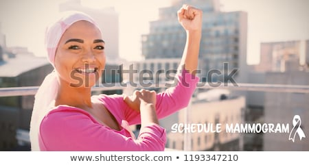 Zdjęcia stock: Confident Woman Standing In City For Breast Cancer Awareness Against Urban Background