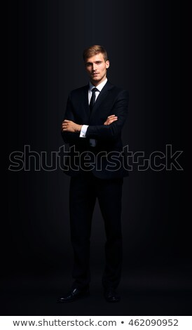 Portrait of confident handsome businessman on black background Stock photo © Traimak